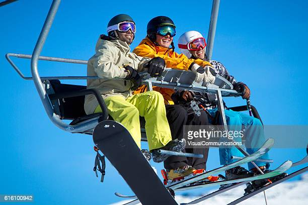 Group of skiers and snowboarders on chair lift.