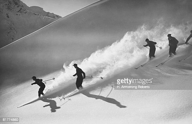 group of skiers descending alpine slope, people in silhouette with sun low on horizon, casting long shadows on snow. - wintersport photos et images de collection
