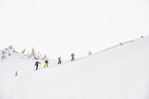 Group of skiers on backcountry ski tour reaching summit of mountain - gettyimageskorea