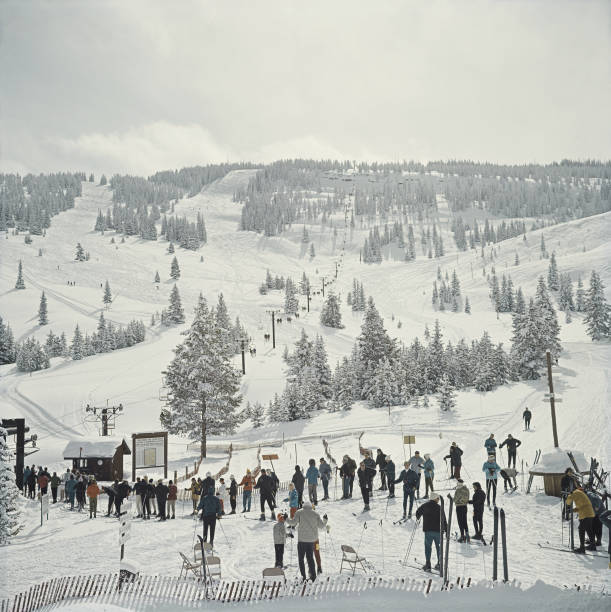 A group of skiers stand in line waiting for the ski...