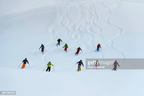A group of skiers turning down a mountain