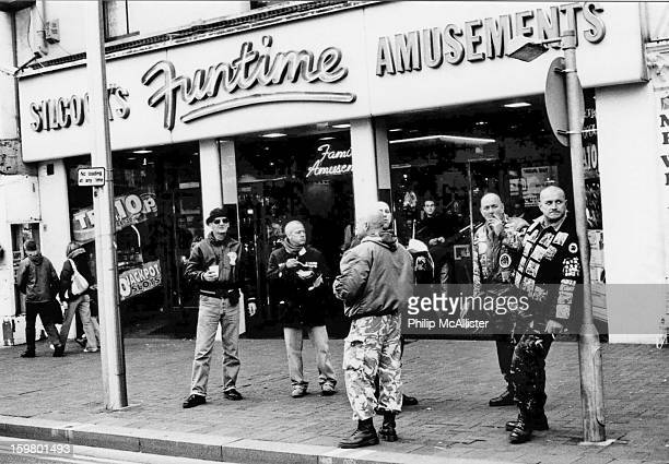Group of skinhead scooterists gather outside an amusement arcade.Some are smoking and some are eating chips.They look nonchalant as one leans...