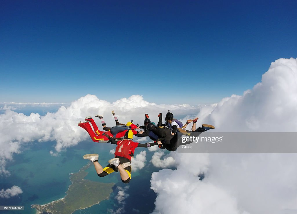 Group of skydivers between clouds and sea : Stock Photo