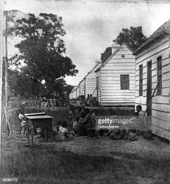 A group of slave children sit around behind the shacks in which they are forced to live on a plantation South Carolina 1860