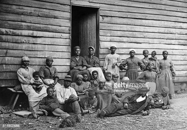 A group of slaves outside their log cabin lodging Undated photograph