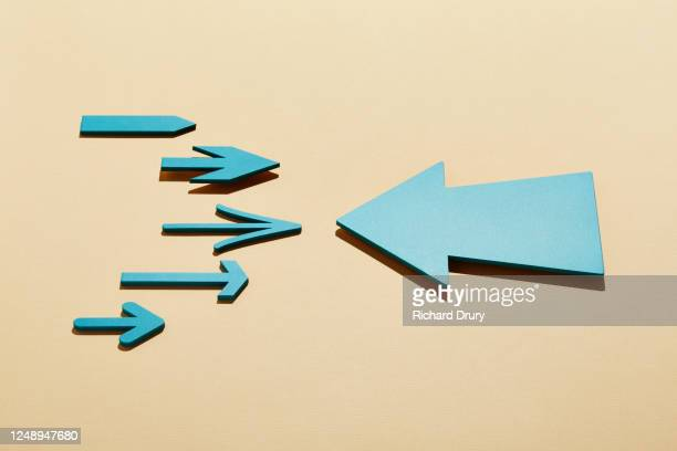 a group of small arrows facing a big arrow - richard drury stock pictures, royalty-free photos & images