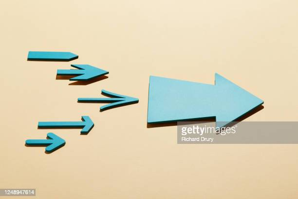 a group of small arrows following a big arrow - richard drury stock pictures, royalty-free photos & images