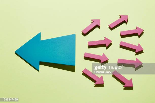 a group of small arrows moving right with a big arrow moving left - beslissingen stockfoto's en -beelden