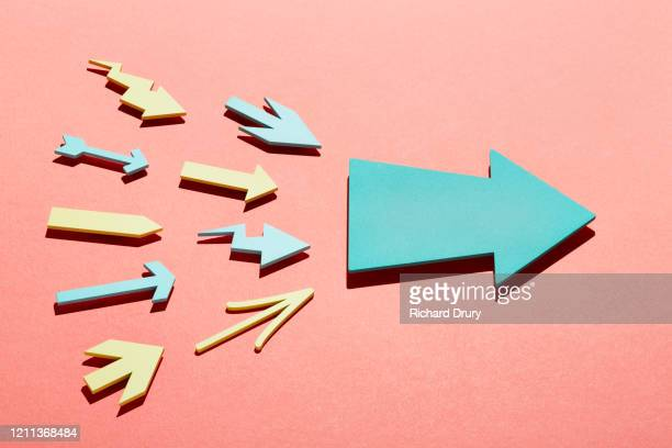 a group of small arrows propelling a big arrow - entschlossenheit stock-fotos und bilder