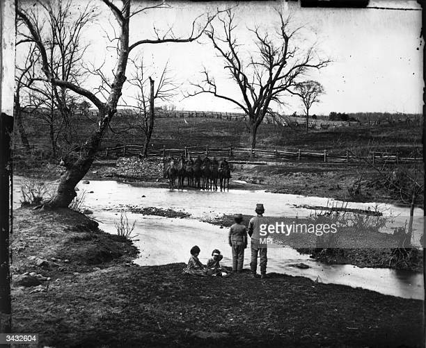 A group of small boys watching Union cavalrymen watering their horses in the stream at Bull Run Manassas Virginia the scene of two battles during the...