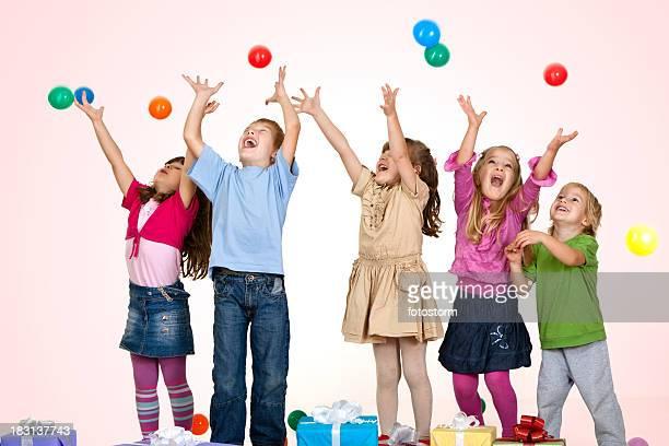 Pequeno grupo de crianças brincando com bolas coloridas em superfície de pavilhão