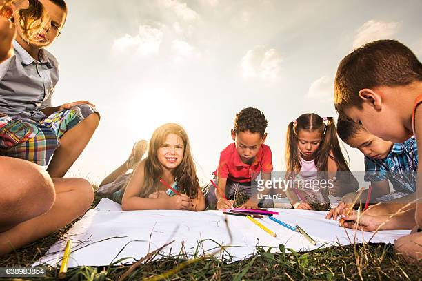Group of small children relaxing in a meadow and coloring.