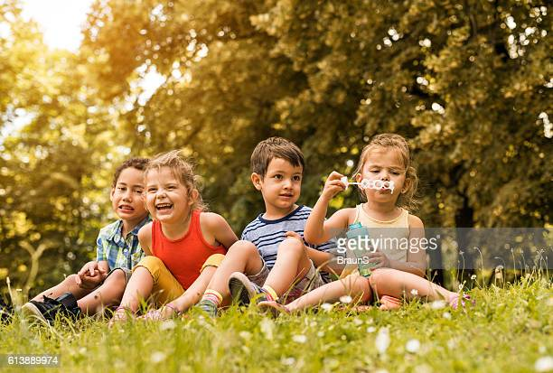 Group of small children relaxing in grass at the park.