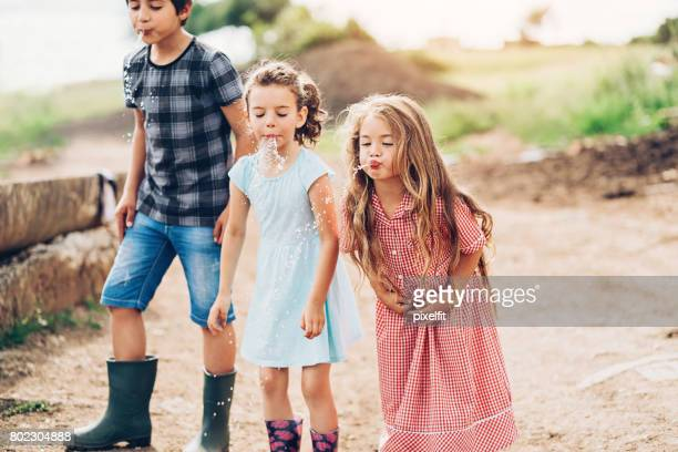 Group of small children spitting water