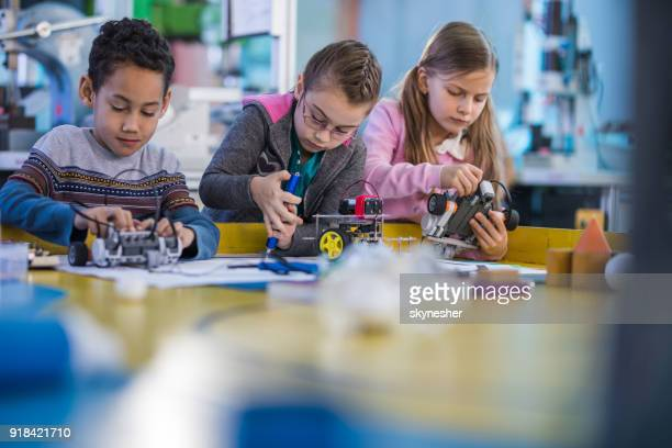 group of small engineers working on innovative robots in school laboratory. - making stock pictures, royalty-free photos & images