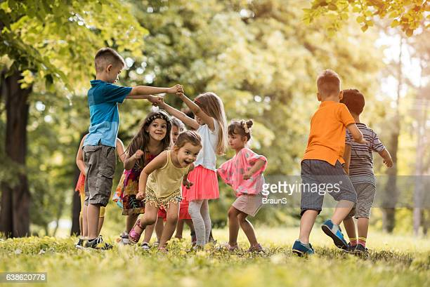 group of small kids having fun while playing in nature. - activiteit bewegen stockfoto's en -beelden