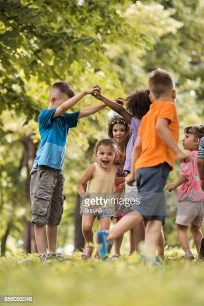 Groupe de petits enfants s'amusant tout en jouant dans la nature.