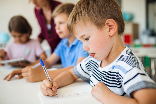 A group of small school kids with teacher in class writing. 1173199025