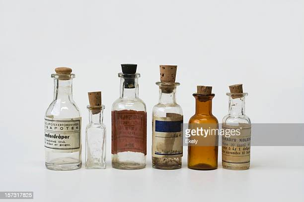 Group of small vintage translucent medicine bottles.