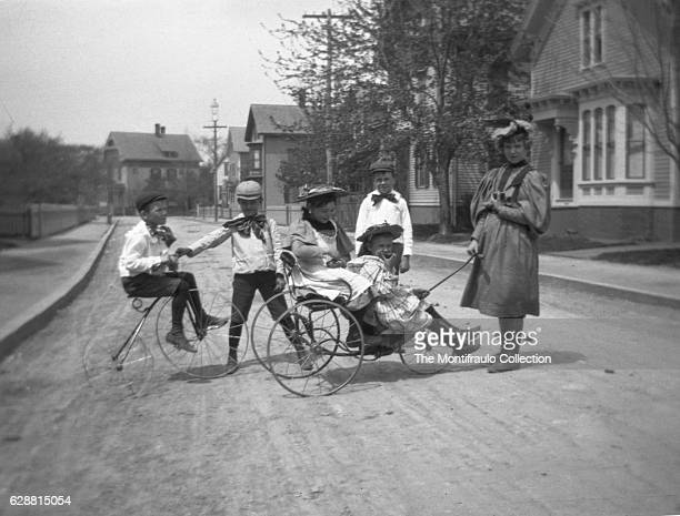 Group of smartly dressed young children playing in the middle of a quiet street on a Velocipede and Tiller and Treadle tricycle; Boston,...