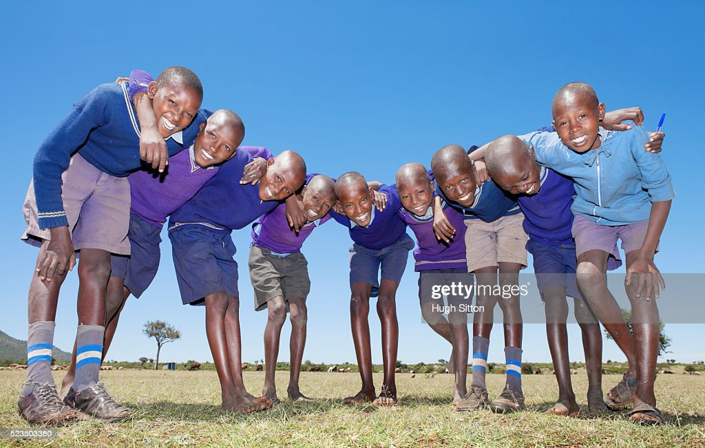 Group of smiling African schoolboys (10-12) huddling against blue sky : Stock Photo