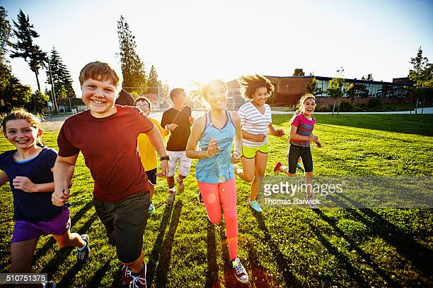 Group of smiling boys and girls running on field