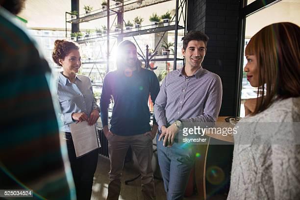 Grupo de sonriendo gente de negocios hablando en la oficina.