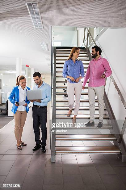 Group of smiling business people in office building hallway.