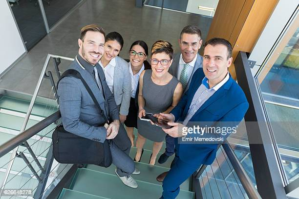 Group of smiling business people standing on the staircase