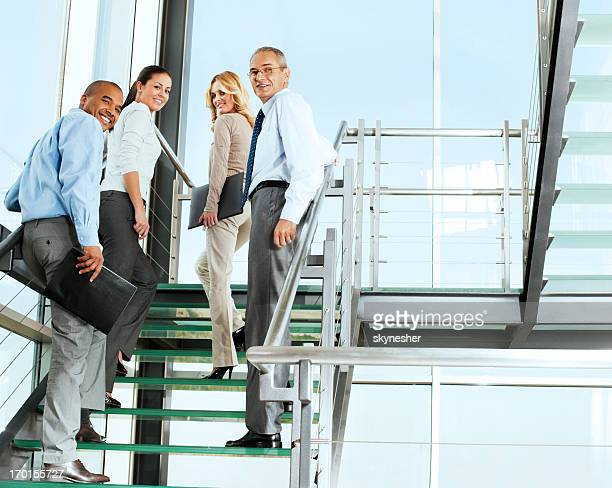 Group of smiling businesspeople people on the staircase.