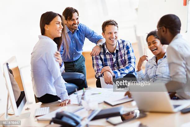 Group of smiling designers relaxing