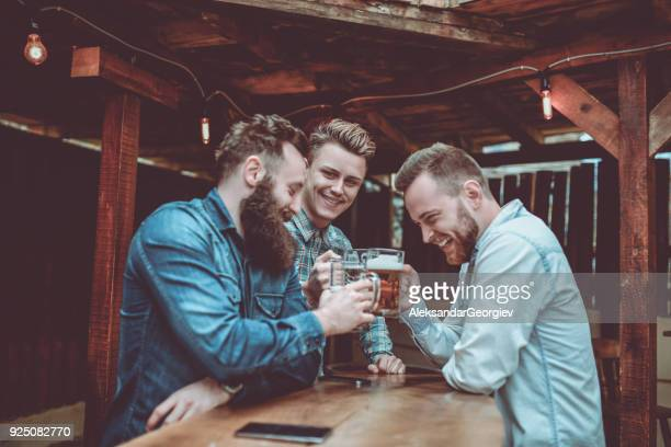 group of smiling friends celebrating with beer - brewery stock pictures, royalty-free photos & images