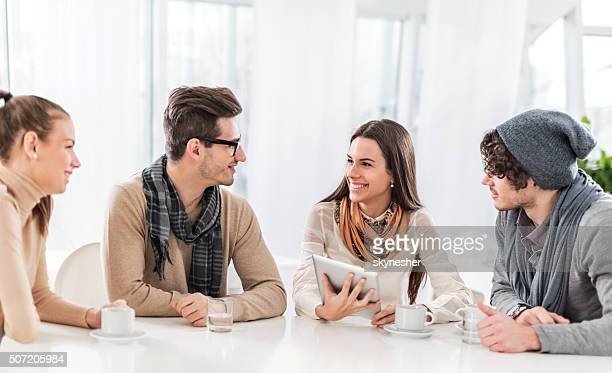 Group of smiling friends communicating in a cafe.