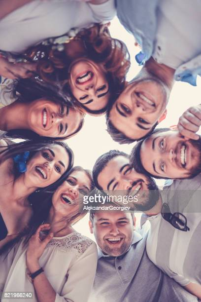group of smiling friends creating circle and looking down - vertical stock pictures, royalty-free photos & images