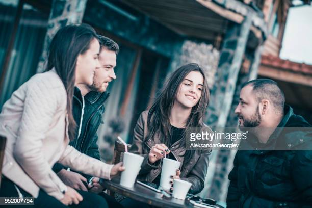 Group of Smiling Friends Having Conversation in a Coffee Restaurant