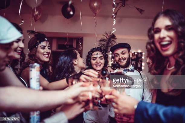 Group of Smiling Friends Having Great Party at Night and Making Toast