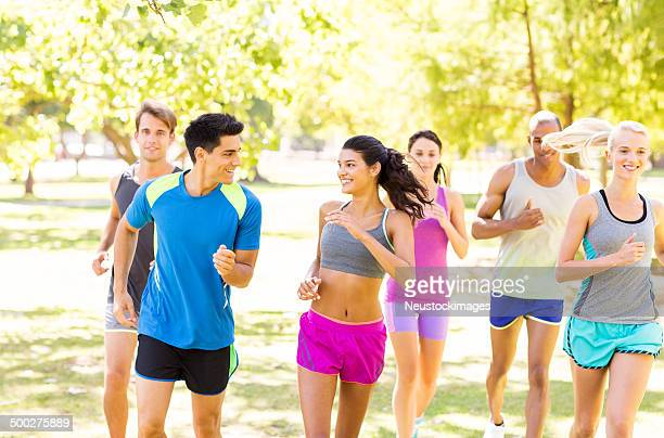 group of smiling friends jogging in park - 5000 meter stock pictures, royalty-free photos & images