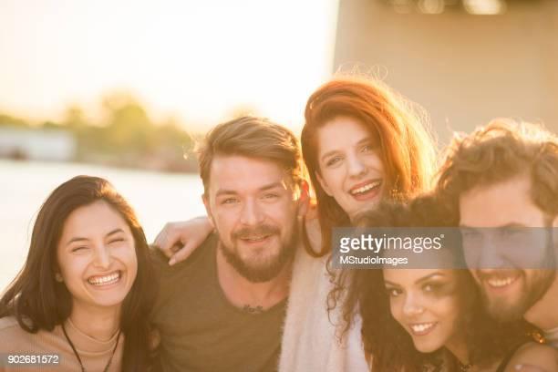Groupe d'amis souriantes regardant la caméra