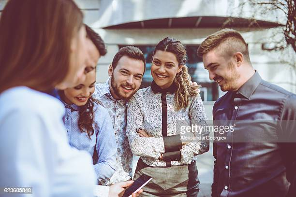 Group of Smiling Friends Sharing Media with Smartphone in City