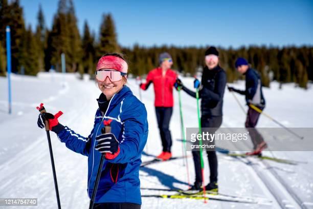 クロスカントリースキー旅行中に休憩を取る笑顔の友人のグループ - クロスカントリースキー ストックフォトと画像