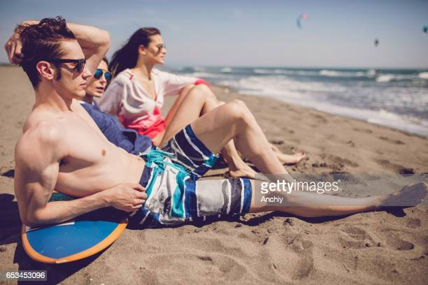Group of smiling friends wearing swimwear and sunglasses with surfboards on beach. Summer concept, friends, friendship, summer fun, young people having fun