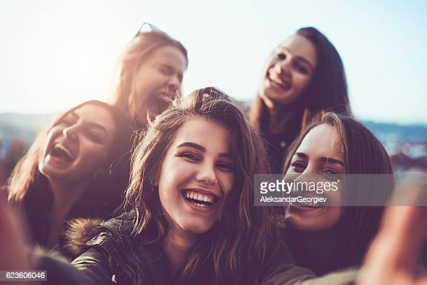 Group of Smiling Girls Taking a Selfie Outdoors at Sunset