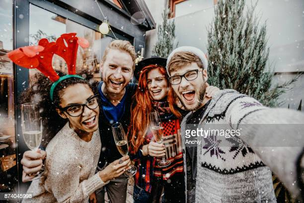 group of smiling men and women taking selfie outdoors while snowing - christmas party stock photos and pictures