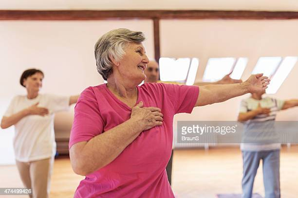 Group of smiling old people doing stretching exercises.
