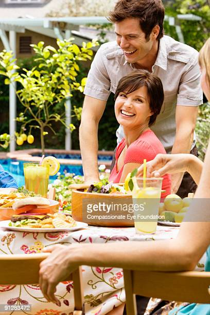 Group of smiling people at table with food