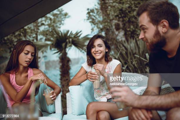 Group of Smiling People Socializing and Drinking Coffee in Backyard
