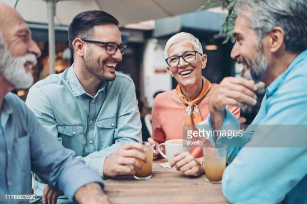 group of smiling people talking in cafe - small group of people stock pictures, royalty-free photos & images