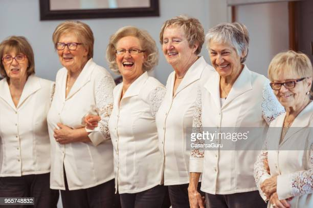 group of smiling senior women standing together - choir stock pictures, royalty-free photos & images