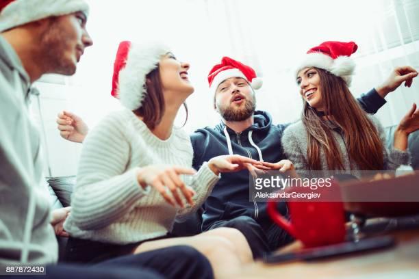 Groupe de sourire chant amis célébrer Noël ensemble à la maison