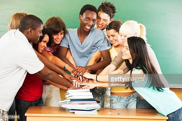 Groupe de souriant étudiants avec leurs mains sommes entassés dans des livres.